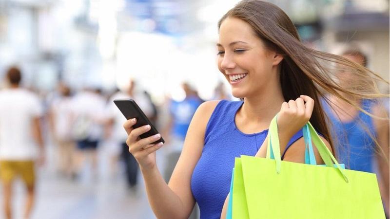 Mulher fazendo compras e usando o celular na África do Sul